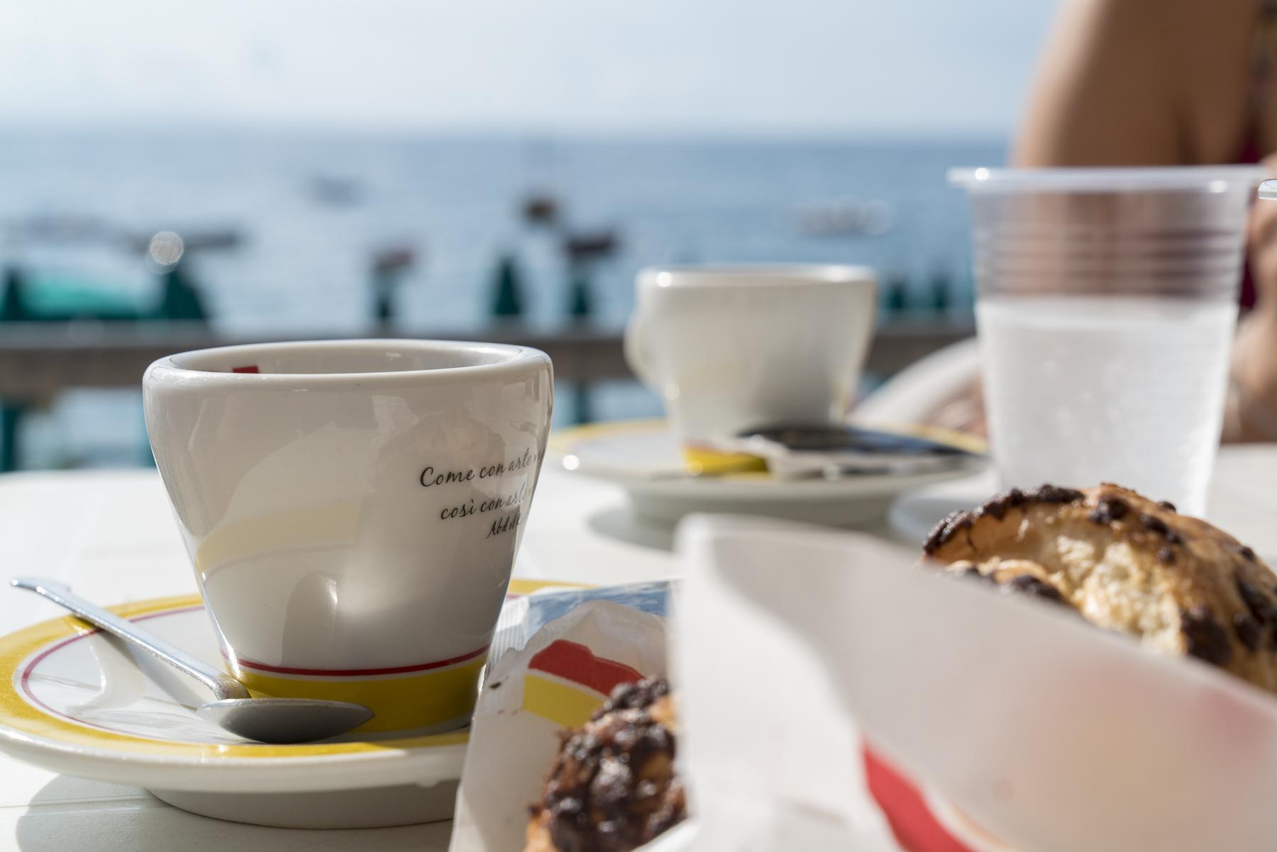 Ein Espresso und eine cornetto am Strand in Italien mit blauem Meer im Hintergrund
