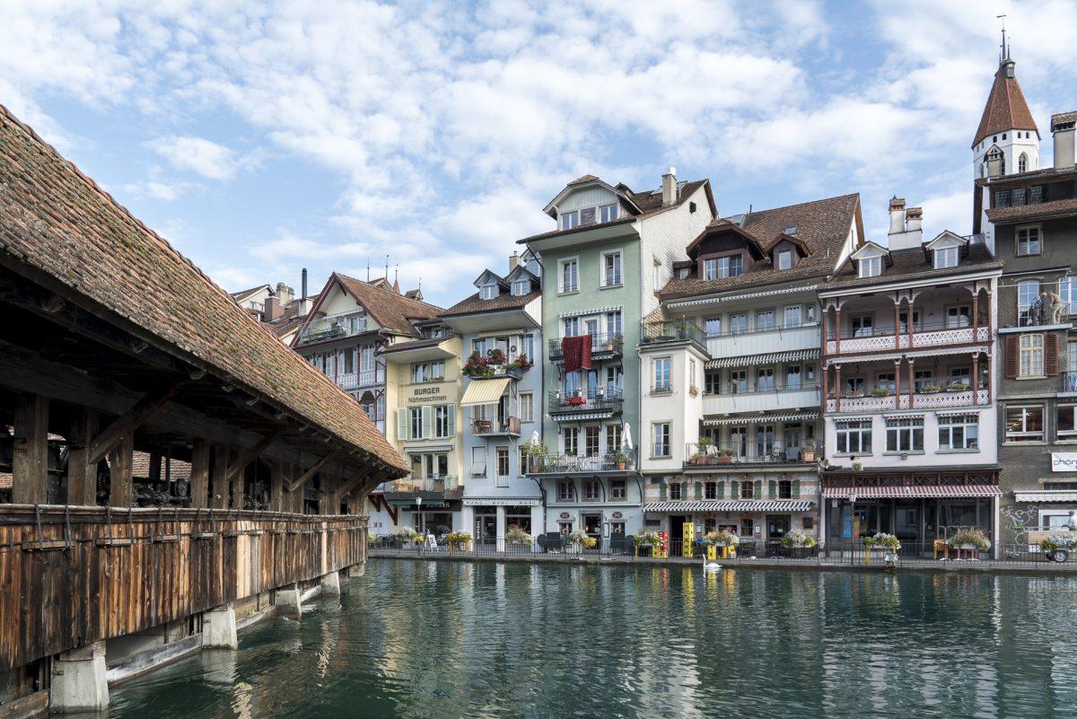 Die Altstadthäuschen von Thun spiegeln sich in der Aare